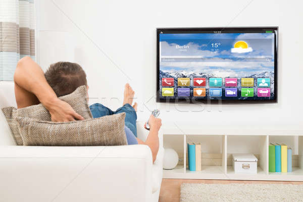 Man Using Remote Control In Front Of Television Stock photo © AndreyPopov