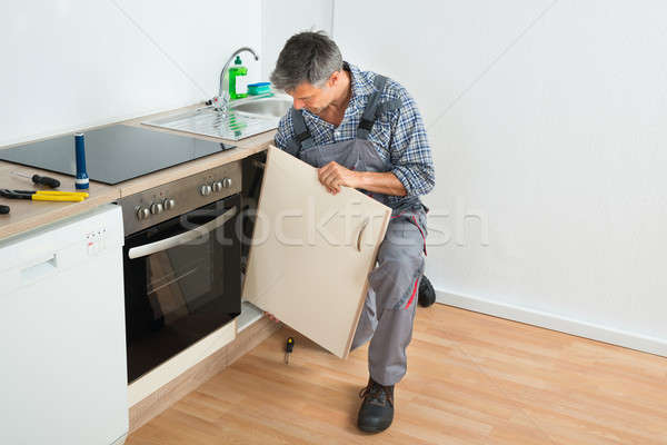 Handyman Fixing Sink Door In Kitchen Stock photo © AndreyPopov
