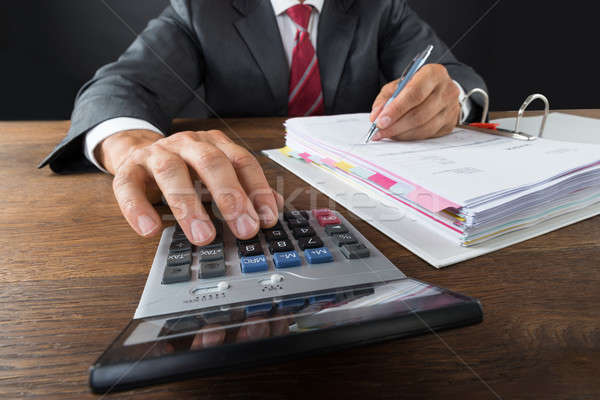 Accountant Checking Invoice With Calculator Stock photo © AndreyPopov