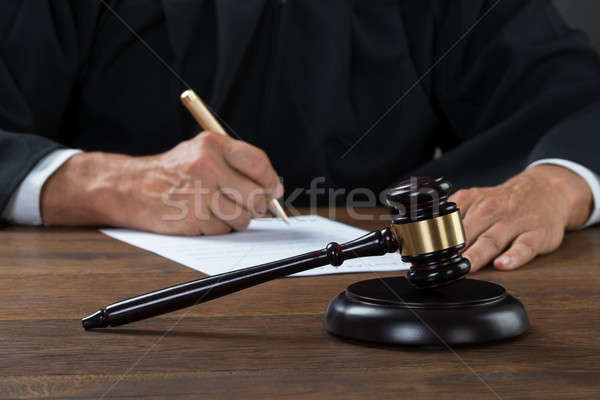 Stock photo: Judge Writing On Paper In Courtroom