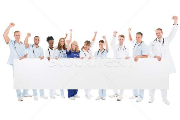 Boldog orvosi csapat karok a magasban tart óriásplakát Stock fotó © AndreyPopov