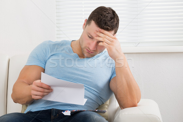 Upset Man Reading Letter On Sofa At Home Stock photo © AndreyPopov