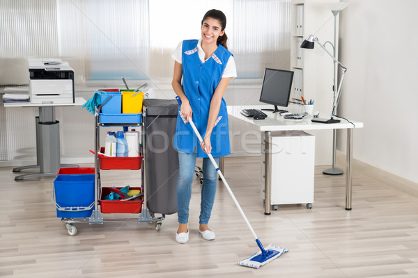 Happy Female Janitor Mopping Floor In Office Stock photo © AndreyPopov