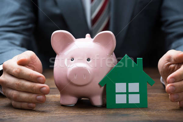 Businessman Protecting Green Paper House And Piggybank Stock photo © AndreyPopov