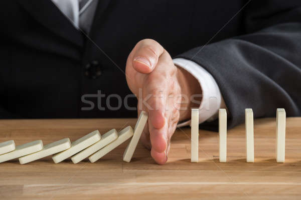 Businessman Stopping Dominoes From Falling Stock photo © AndreyPopov
