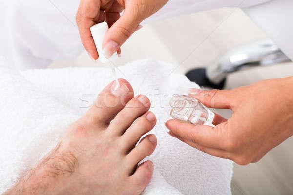 Manicurist Applying Moisturizing Oil On Person's Toenail Stock photo © AndreyPopov