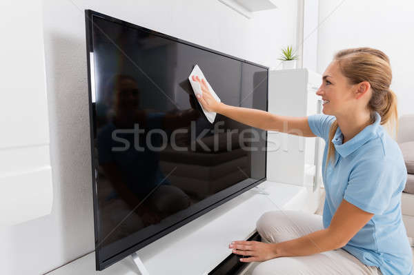 Woman Wiping Television Of Living Room Stock photo © AndreyPopov