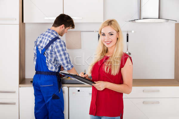 Smiling Woman Signing Invoice From Male Plumber Stock photo © AndreyPopov
