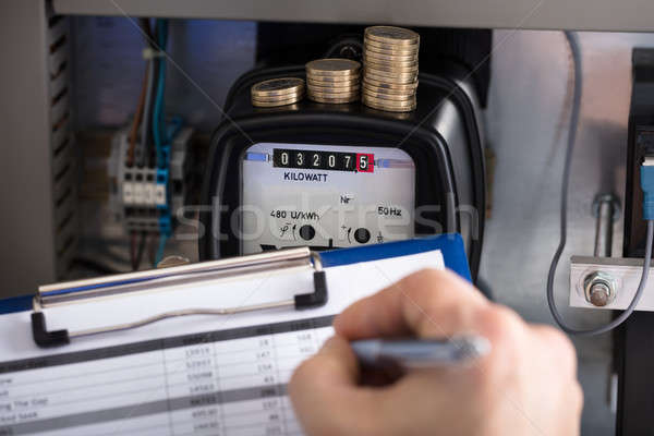 Technician Hand Writing Reading Of Meter Stock photo © AndreyPopov