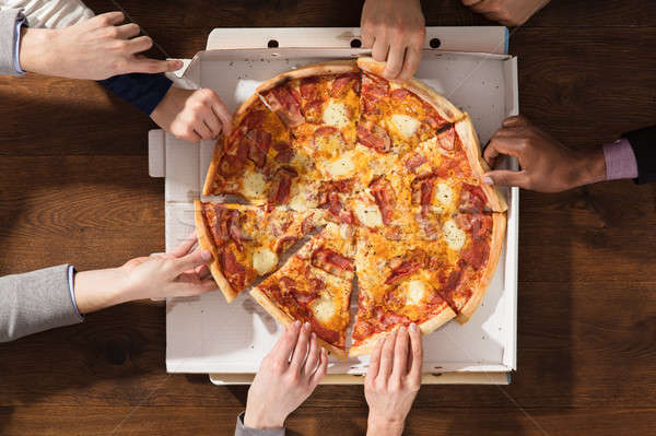 Hands Taking Each Slice Of Pizza Stock photo © AndreyPopov