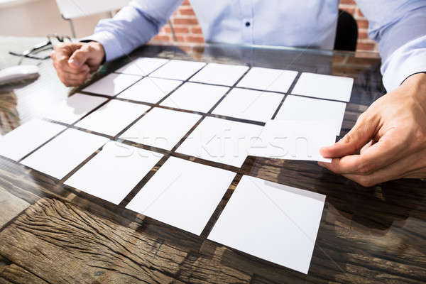 Businessman Arranging Adhesive Notes On Desk Stock photo © AndreyPopov