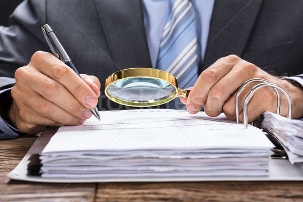 Businessman Examining Invoice With Magnifying Glass Stock photo © AndreyPopov
