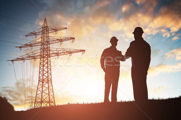 Two Engineers Shaking Hands Against Dramatic Sky Stock photo © AndreyPopov