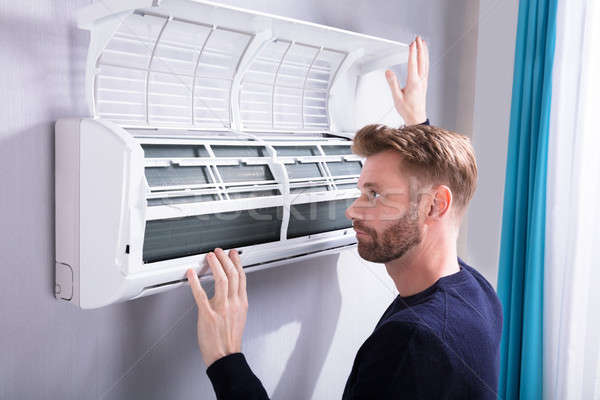 Young Man Checking Air Conditioner Stock photo © AndreyPopov