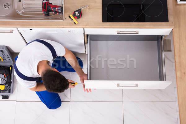 Carpenter Fixing Drawer In Kitchen Stock photo © AndreyPopov