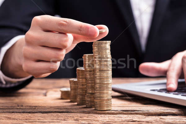 Businessperson Placing A Coin On Increasing Coin Stacks Stock photo © AndreyPopov