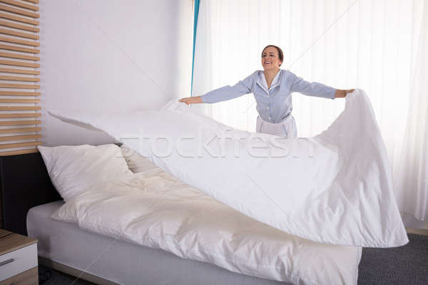 Házvezetőnő ágy mosolyog fiatal női hotelszoba Stock fotó © AndreyPopov
