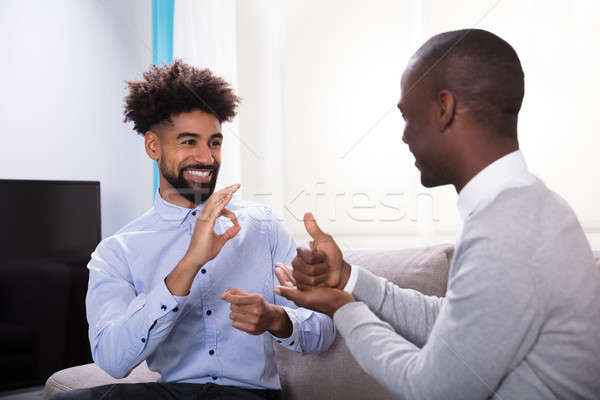 Dois feliz homens linguagem gestual jovem Foto stock © AndreyPopov