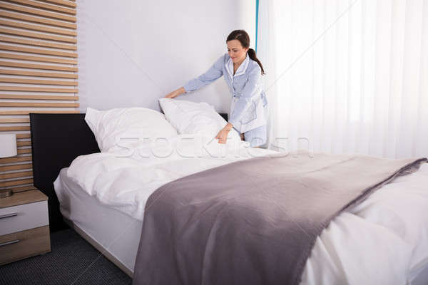 Housekeeper Arranging Pillow On Bed Stock photo © AndreyPopov