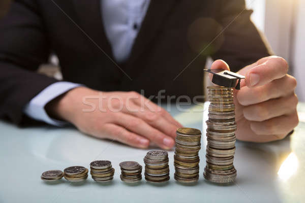 Businessperson Placing Graduation Hat On Top Of Stacked Coins Stock photo © AndreyPopov