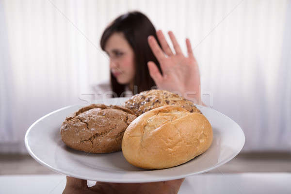 Woman Refusing Plate Of Bread And Cookies Stock photo © AndreyPopov