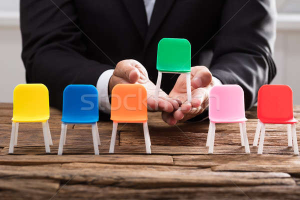 Businessperson's hand picking up green chair Stock photo © AndreyPopov