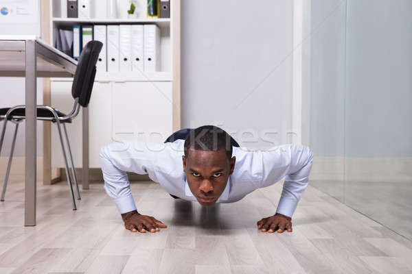 Stock photo: Businessman Doing Pushup In The Office