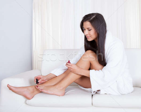 Stock photo: Woman varnishing her toenails