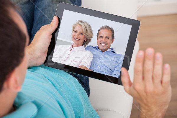 Man Having Video Chat With Parents On Digital Tablet Stock photo © AndreyPopov