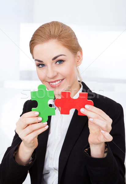 Businesswoman Holding Jigsaw Puzzle Stock photo © AndreyPopov