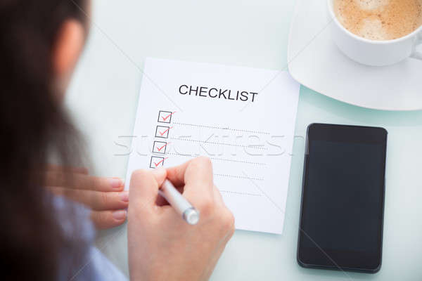 Businesswoman Marking On Checklist Stock photo © AndreyPopov