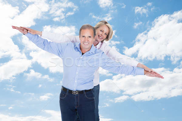 Couple With Arms Outstretched Standing Against Cloudy Sky Stock photo © AndreyPopov