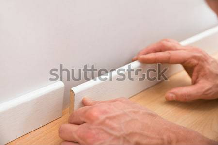 Person Applying Skirting On Wall Stock photo © AndreyPopov