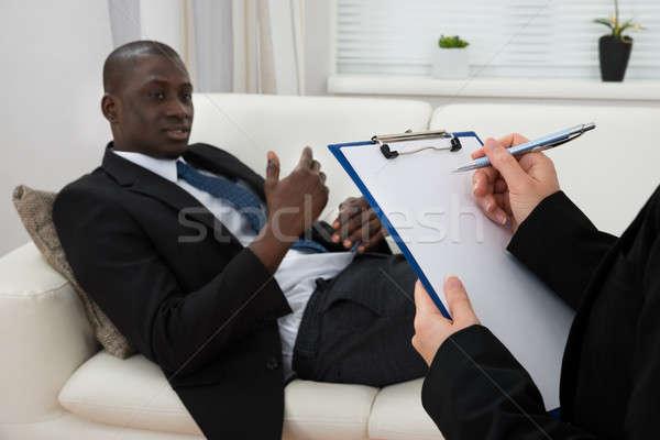 Patiënt bank psychiater schrijven afrikaanse Stockfoto © AndreyPopov
