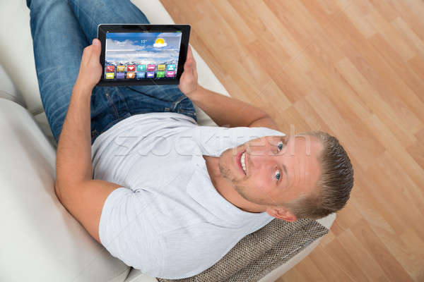Man On Sofa With Laptop Showing Icons Stock photo © AndreyPopov