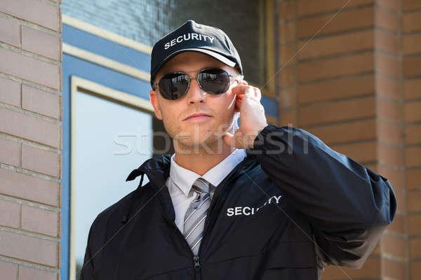 Genç güvenlik görevlisi ayakta giriş dinleme Stok fotoğraf © AndreyPopov