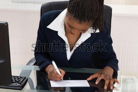 Femme d'affaires signature chèque jeunes africaine Photo stock © AndreyPopov