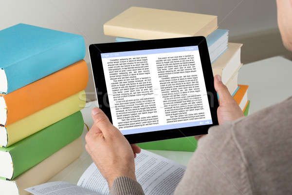 Student Holding Ereader While Studying At Desk Stock photo © AndreyPopov