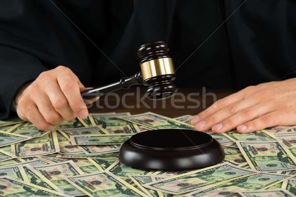 Corrupt Judge Hitting Gavel With Banknotes Spread At Desk Stock photo © AndreyPopov