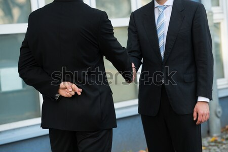 Businessman Holding Dollars While Shaking Hands With Partner Stock photo © AndreyPopov