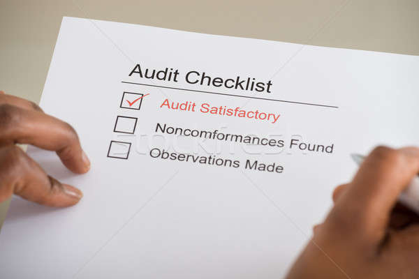 Stock photo: Person's Hand Filling Audit Checklist Form