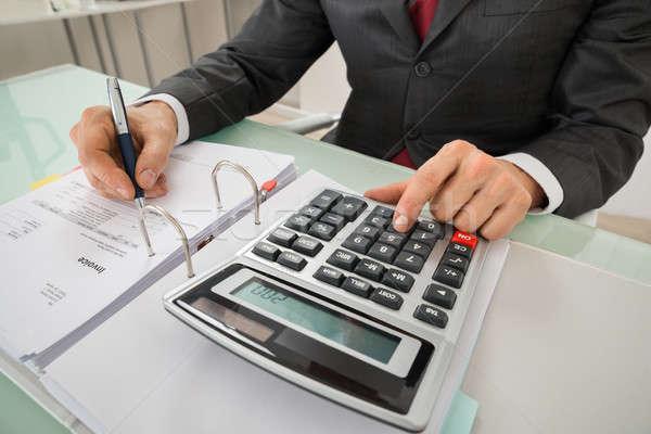 Close-up Of Businessman Calculating Invoice Using Calculator Stock photo © AndreyPopov