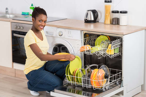 Happy Woman Arranging Plates In Dishwasher Stock photo © AndreyPopov