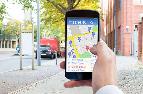 Person Hand Using GPS Navigation On Mobile Phone To Find Hotels Stock photo © AndreyPopov