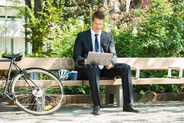 Businessman Sitting On Bench Using Laptop Stock photo © AndreyPopov