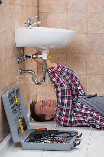 Plumber Lying On Floor Fixing Sink Stock photo © AndreyPopov
