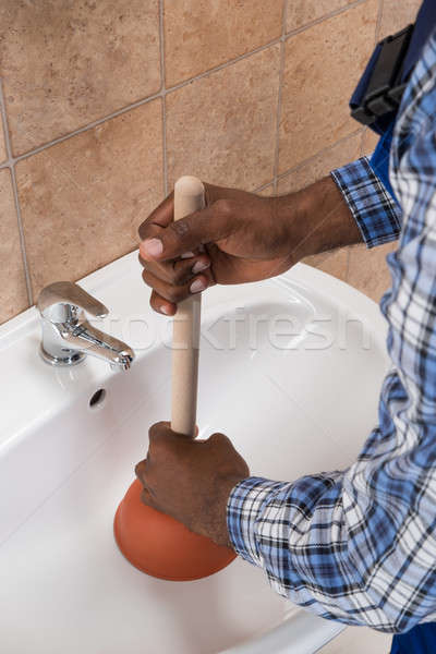 Plumber's Hand Using Plunger In Bathroom Sink Stock photo © AndreyPopov