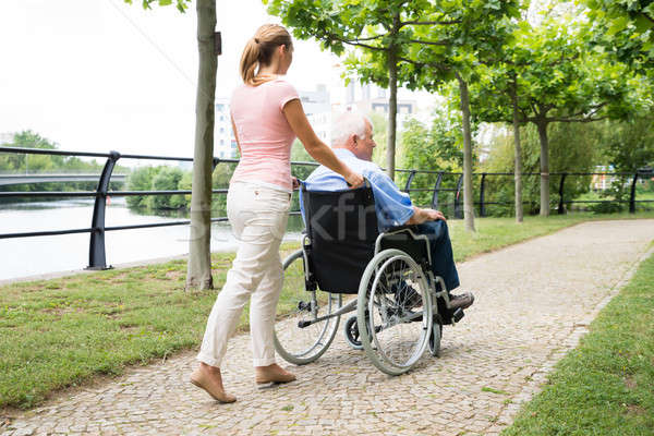 Smiling Young Woman Assisting Her Disabled Father On Wheelchair Stock photo © AndreyPopov