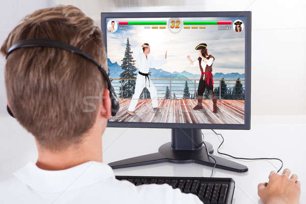 Man Playing Fighting Game On Desktop Stock photo © AndreyPopov
