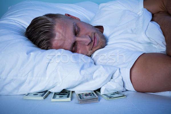 Homem adormecido moeda notas travesseiro Foto stock © AndreyPopov